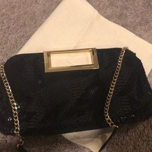 Michael Kors clutch handbag with crossbody strap.